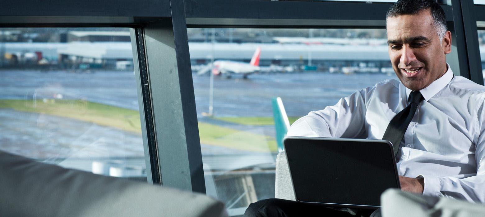Man using his laptop at an airport