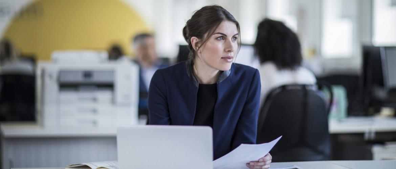 Nainen istuu toimistossa läppärin takana