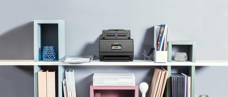 ADS-3600W desktop document scanner on shelf with notebooks