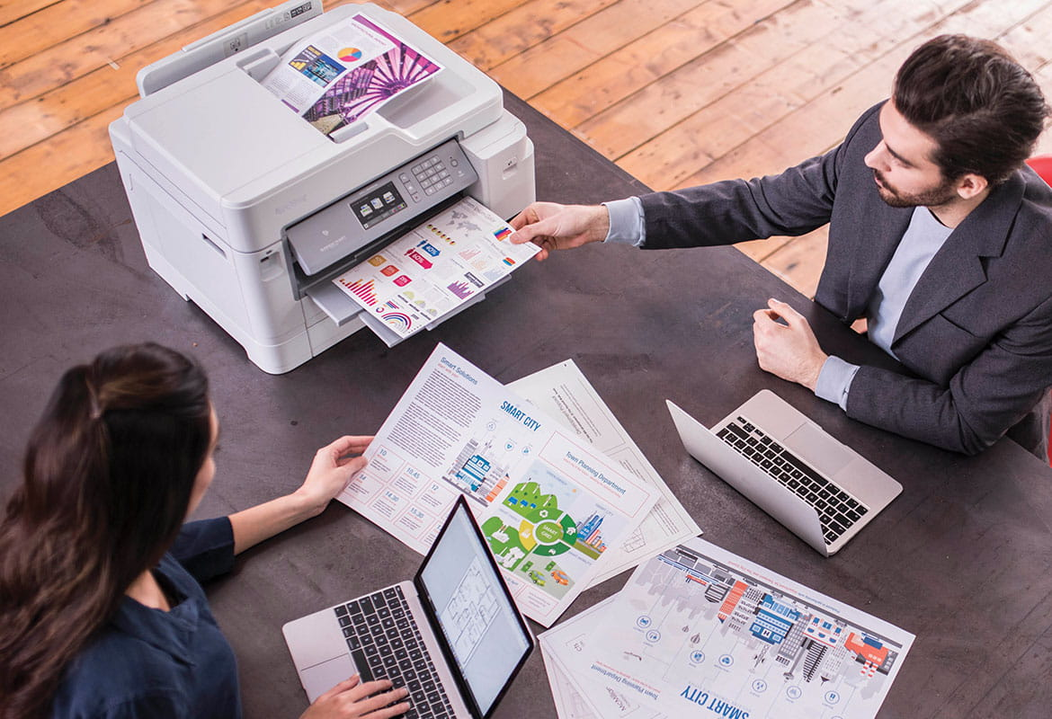 Man and woman sat at desk printing colour documents