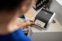 Nurse printing patient label using Brother TD-4410D desktop label printer
