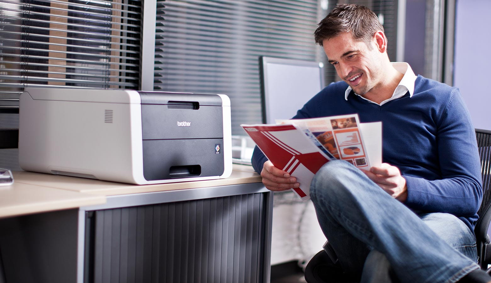 Man-reading-magazine-next-to-colour-printer