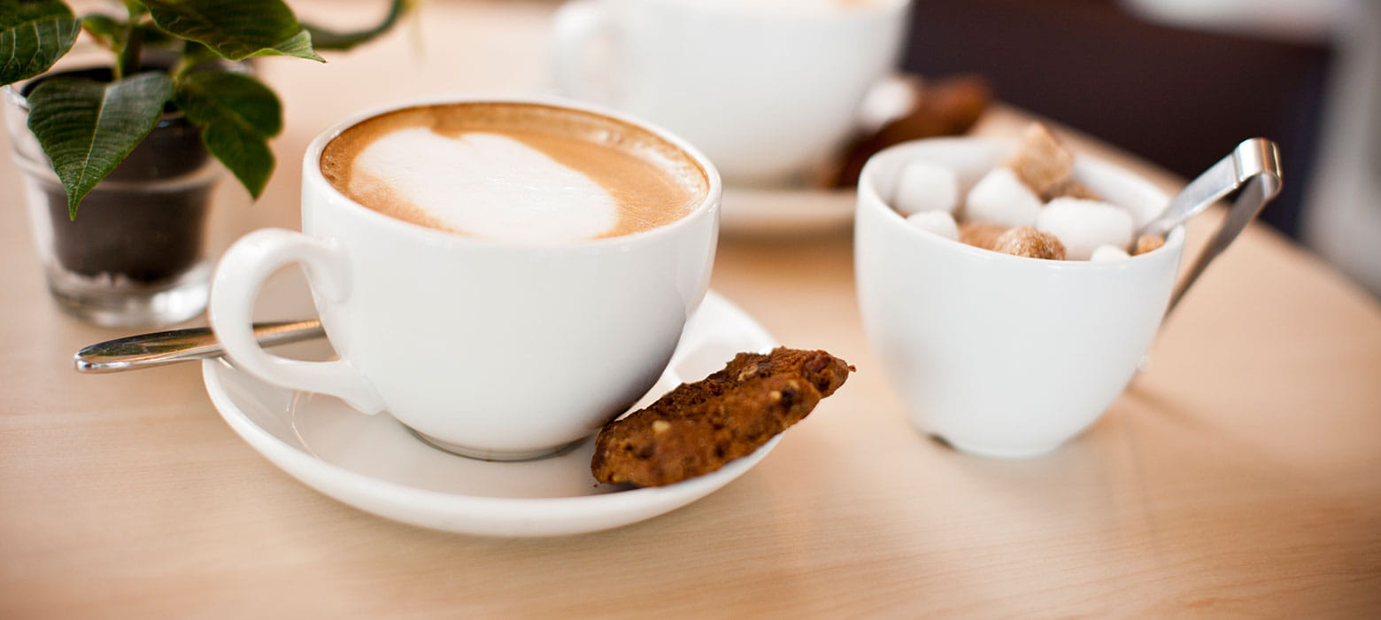 cup of coffee in a saucer with a biscuit
