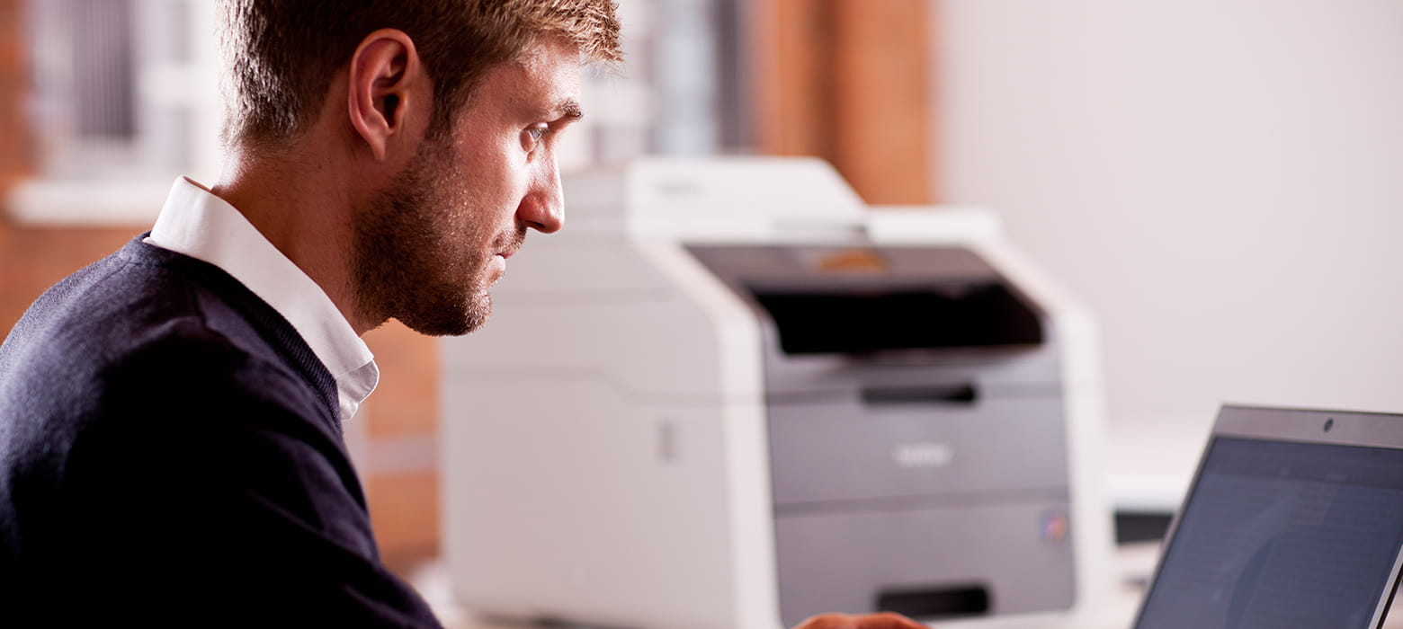Man on a computer with a Brother printer in the backround