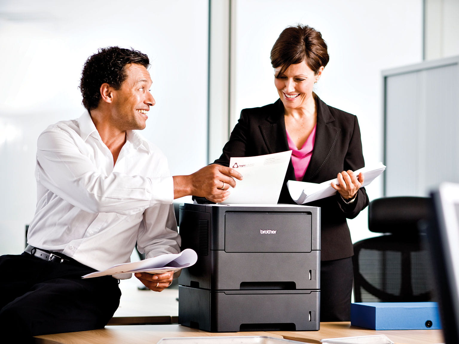 man and woman chatting next to a Brother printer