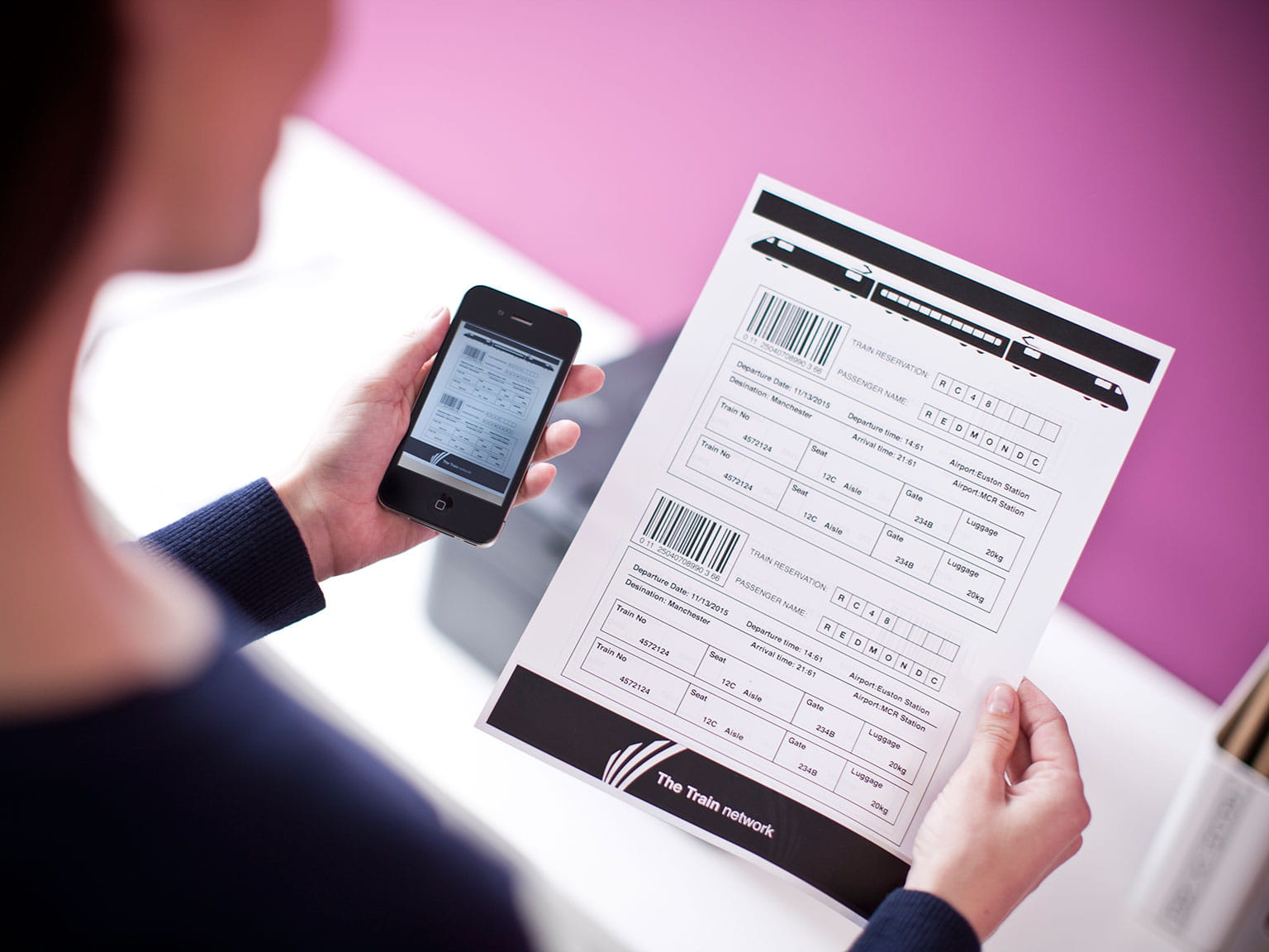 person holding up their phone next to a document